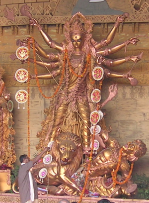 this is an essay about the role of idol worship for hindu women in  durga slaying mahisasur golden statue the priest is performing navami arati in front